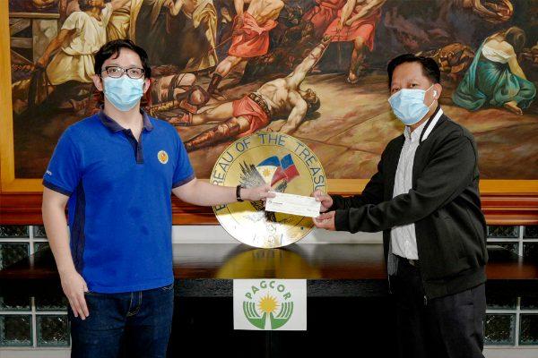 Вице-президент PAGCOR по финансам Ректо Бальтазар-младший (справа) передает чек на сумму 1 миллиард песо исполняющему обязанности сотрудника Казначейства и директору службы управления ак